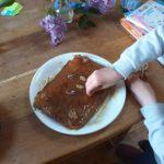 Yanis décore son gâteau après cuisson.